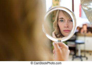 Client in hairdresser salon watches herself in mirror -...