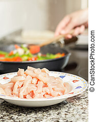 Closeup of raw chicken dish and female cooking vegetables in a black pan in the background
