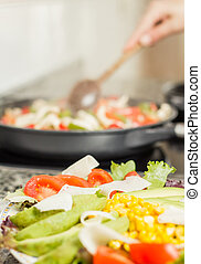 Closeup of fresh salad dish and female cooking in a pan