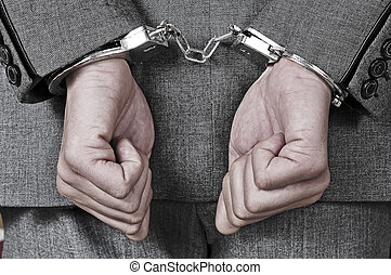 handcuffed man - a man wearing a suit, with handcuffs in his...