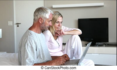 Couple using laptop together and chatting in bedroom