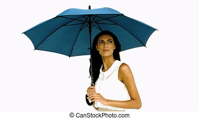 Pretty woman under blue umbrella cowering with fear on white...
