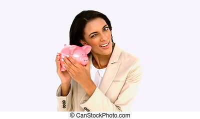 Businesswoman shaking piggy bank on white background in slow...