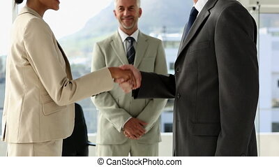 Business people shaking hands in office with boss watching