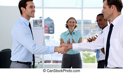 Businessmen shake hands while other business people...