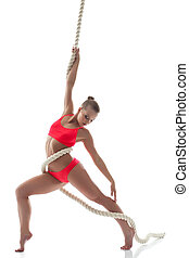Slender young girl hanging on rope in studio