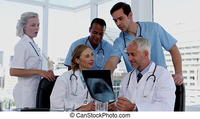 Group of doctors examining an x-ray together in a meeting...