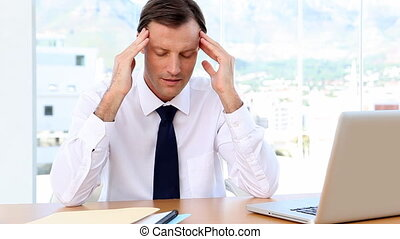 Businessman having a headache in his office sitting at desk
