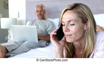 Woman laughing while she is on the phone next to his husband...