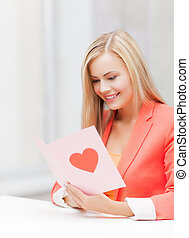 woman holding postcard with heart shape - picture of woman...