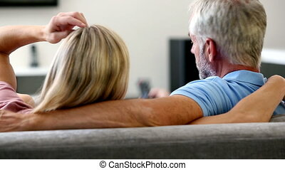 Mature couple watching television and changing channel
