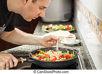 Man cooking vegetables and chicken in a pan - Handsome man...