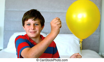 Boy piercing his balloon in the bedroom