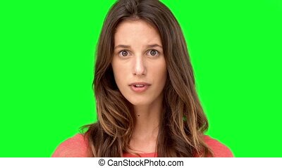 Woman cowering with fear on green screen in slow motion