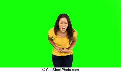 Woman suffering from belly pain on green screen in slow...