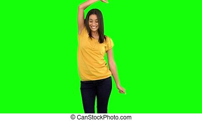 Woman dancing with arms raised on green screen in slow...