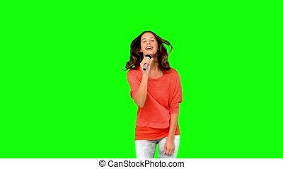 Young woman singing in microphone in slow motion