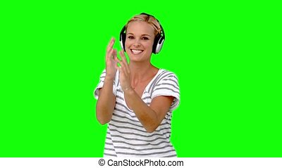 Young woman listening to music on green screen in slow...