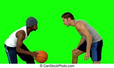 Men playing at basketball in slow motion on green screen