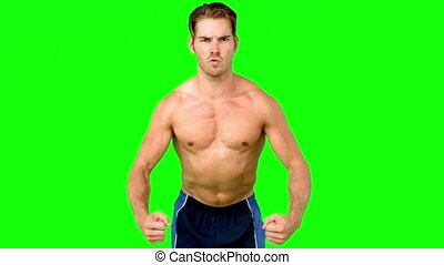 Shirtless serious man flexing muscles in slow motion on...