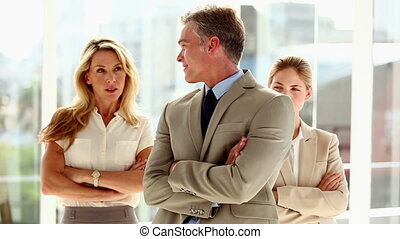 Businessman looking to businesswomen in bright office