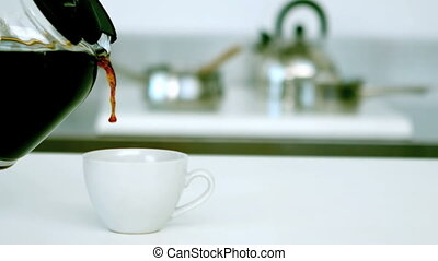 Coffee being poured into cup of cof