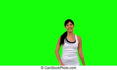 Woman in sportswear stretching her arms on green screen in...