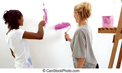 Two women painting on white wall in slow motion