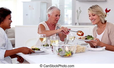 Mature woman serving meal to her friends in the dinning room
