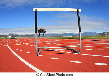 Overcoming Obstacles - A hurdle sits on a track in a high...