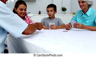 Grandparents playing cards with their grandchildren at home...