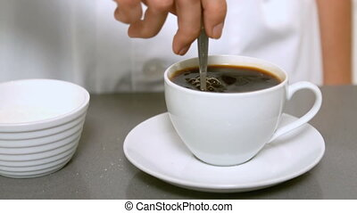 Hand stirring cup of coffee close up in slow motion