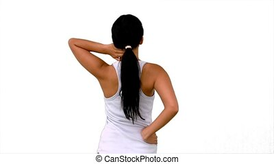 Fit woman stretching her neck and back on white background...