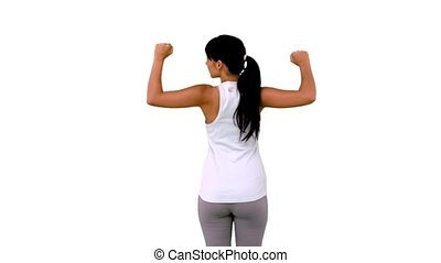 Fit woman tensing arm muscles rear view on white background...