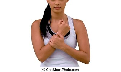 Fit woman massaging her sore wrist on white background in...