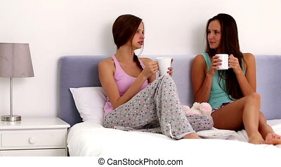 Friends chatting and drinking coffee sitting up in bed...
