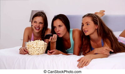 Friends eating popcorn and watching tv on bed in their...