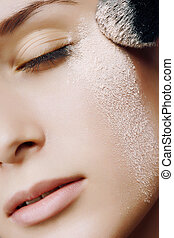 Young beautiful woman with a powder on the face