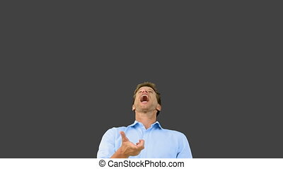 Man catching an orange segment with his mouth on grey screen...