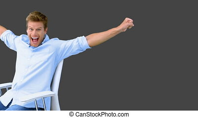 Man on swivel chair raising arms to show his success on grey...