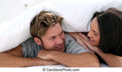 Attractive couple cozy under the covers and smiling at...