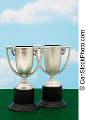 Trophies - Two trophies on green with sky background