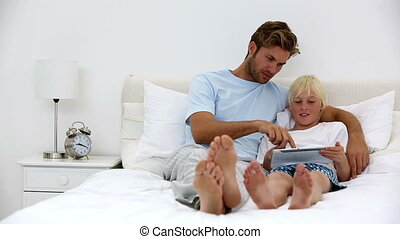 Father and son using tablet together at home on bed