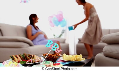 Pregnant woman receiving her guests at her baby shower at...