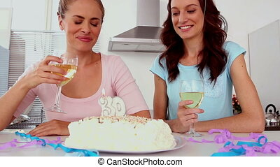 Woman blowing out candle on her birthday cake with her...