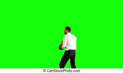 Businessman leaping with boxing gloves and punching on green...