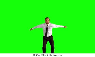Businessman jumping up and doing the splits on green screen...