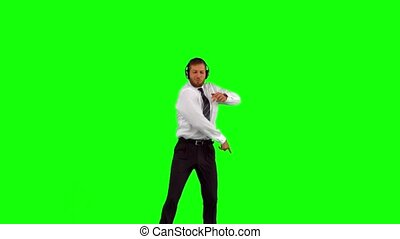 Businessman listening to music while jumping up disco...