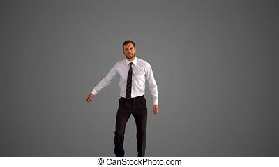 Businessman jumping and clicking heels on grey background in...