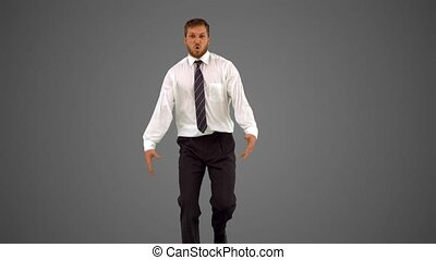 Businessman walking towards camera and dancing funnily on...